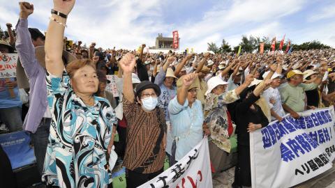 Des manifestants le poing levé au rassemblement qui a eu lieu à Okinawa, dimanche.