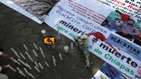 Des chandelles sont allumées à côté d'une banderole montrant la photo de Mariano Abarca Roblero.