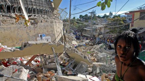 Jeune Haïtienne devant des édifices démolis