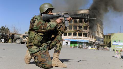 Un soldat prend position devant un centre commercial en feu à Kaboul.