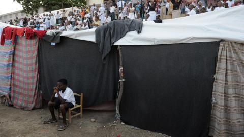 Jeune garçon devant un abri de fortune à Port-au-Prince.
