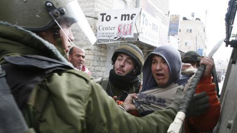 Des soldats israéliens tentent d'immobiliser des manifestants palestiniens.
