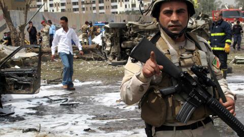 Des secouristes et des policiers inspectent la scène d'un attentat près de l'ambassade d'Iran, au centre de Bagdad, le 4 avril 2010.
