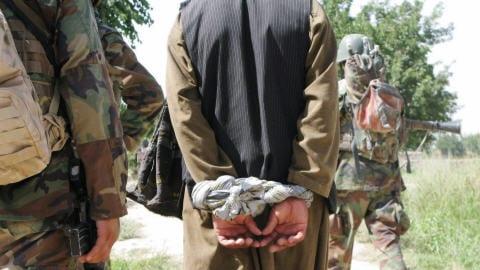 Un homme arrêté lors d'une patrouille conjointe des armées canadienne et afghane est emmené pour interrogatoire.
