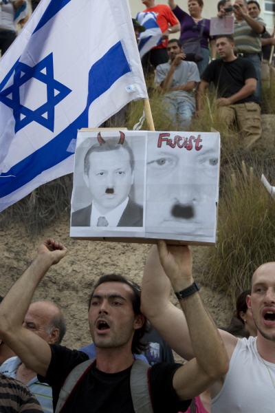 Des manifestants israéliens devant l'ambassade turque à Tel-Aviv brandissant une photo du premier ministre turc caricaturé avec une moustache à la Hitler avec l'inscription fasciste.