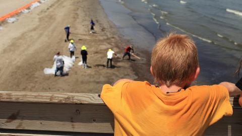Un garçon de 9 ans observe les opérations de nettoyage sur la plage où il a l'habitude de passer une partie de ses étés.