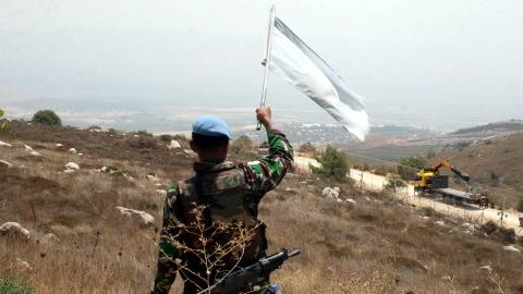 Un soldat de la FINUL agite le drapeau de l'ONU en direction de soldats israéliens avant les affrontements.