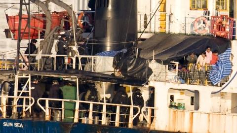 Des Tamouls (en haut à droite) observent des agents de la GRC montés à bord du MV Sun Sea.