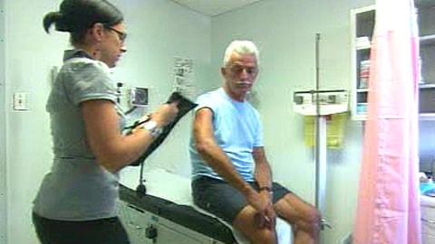 Une infirmière praticienne prend la tension artérielle d'un patient.