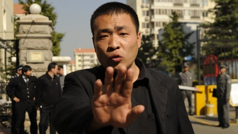 Un policier chinois en civil tente d'empêcher la prise de photos à l'extérieur de la résidence de la femme de Liu Xiaobo.