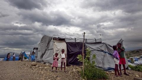 Des enfants devant leur abri dans un camp de réfugiés installé à la suite du séisme de janvier dernier à Port-au-Prince.