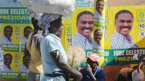 Une Haïtienne et son fardeau devant des affiches électorales du candidat Jude Celestin, le 23 novembre 2010, à Petion-Ville.