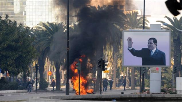 De la fumée s'élève dans le ciel de Tunis pendant des affrontements entre policiers et manifestants, le 14 janvier 2011.