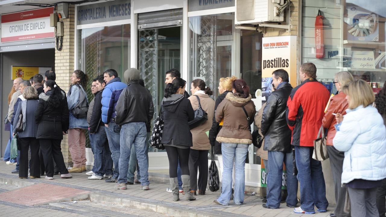 À Madrid en Espagne, des travailleurs attendent devant un bureau de chômage.