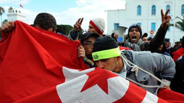 Des habitants de Kasserine, une région centrale de Tunisie, embrassent un drapeau du pays lors d'une manifestation devant le palais du gouvernement à Tunis.