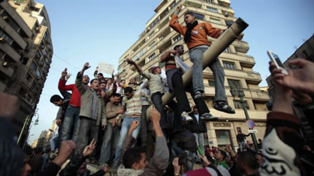 Des manifestants sur un char d'assaut au Caire.