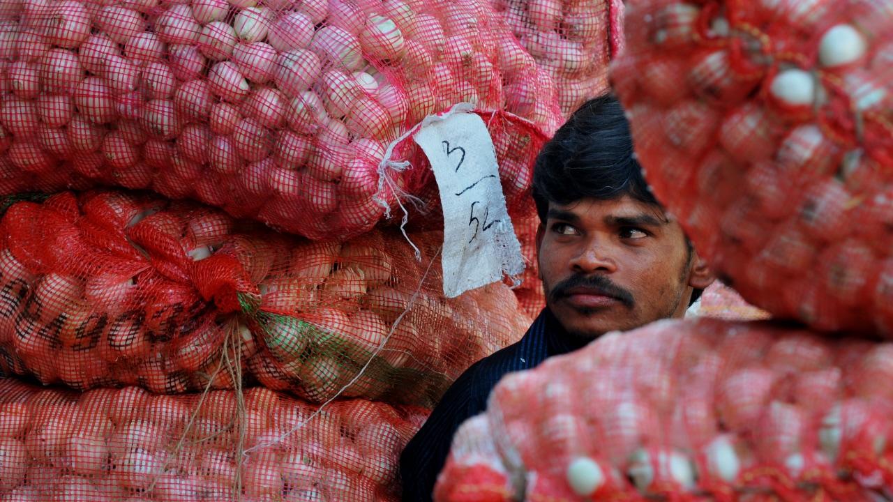 Un travailleur indien au milieu de sacs d'oignons
