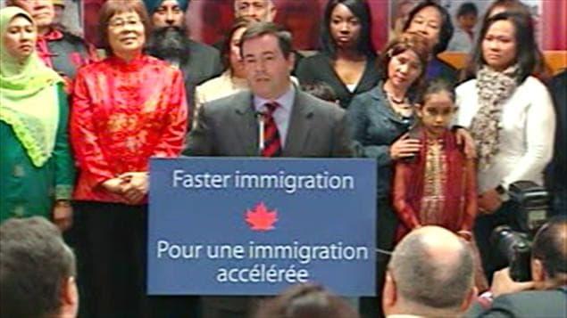 Le ministre Kenney entouré d'immigrants