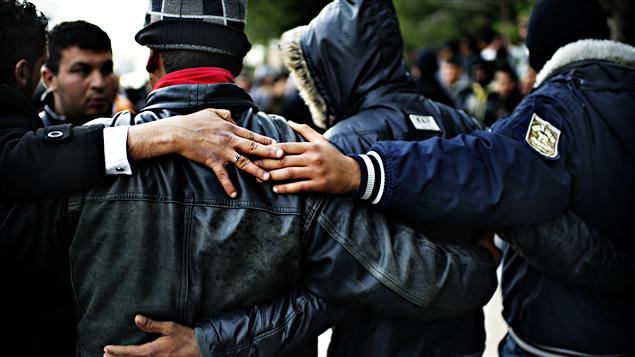 Des immigrants clandestins tunisiens s'enlacent après leur arrivée sur l'île italienne de Lampedusa, le 14 février 2011.