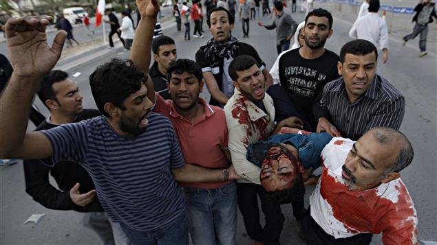 Un homme gravement blessé est trasnporté par d'autres manifestants.