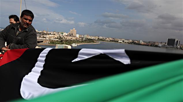 Un manifestant étend l'ancien drapeau national au sommet d'un hôtel à Benghazi.