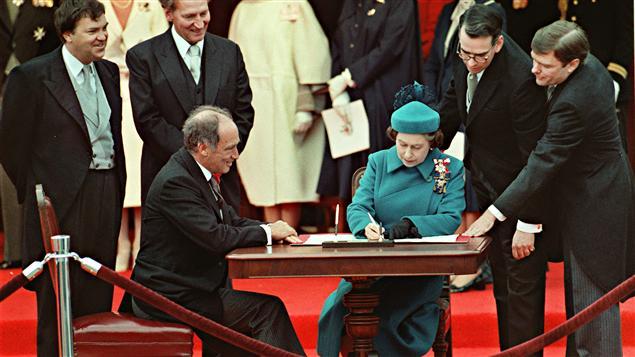 Signature de la Constitution canadienne par la reine Elizabeth II à Ottawa, le 17 avril 1982, en présence du premier ministre Pierre Trudeau