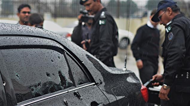 Des policiers inspectent la voiture criblée de balles du ministre des Minorités religieuses, Shahbaz Bhatti.