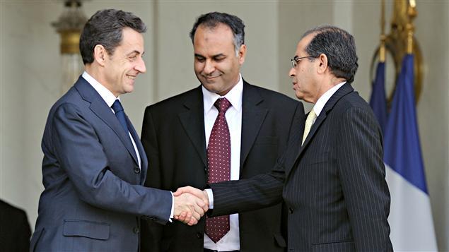 Le président français Nicolas Sarkozy serre la main d'Ali Essaoui (à droite) à l'Élysée. Au centre, l'autre émissaire du CNT, Mahmud Jibril.