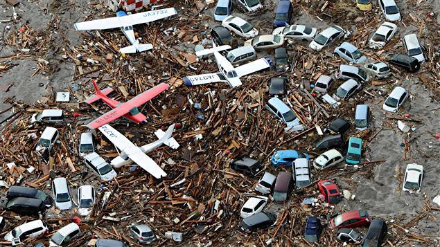 Des voitures et des petits avions emportés par le tsunami à Sendai, dans le nord du Japon.