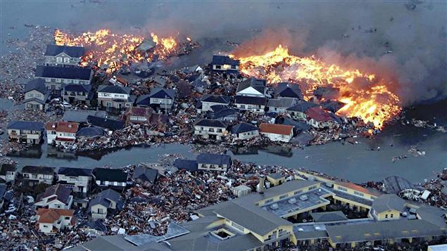 Les flammes et les flots s'affrontent de façon saisissante à Natori, dans la préfecturede Miyagi.