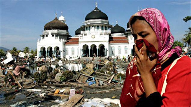 Une femme marche au milieu des décombres près de la mosquée de Banda Aceh, en Indonésie en décembre 2004.