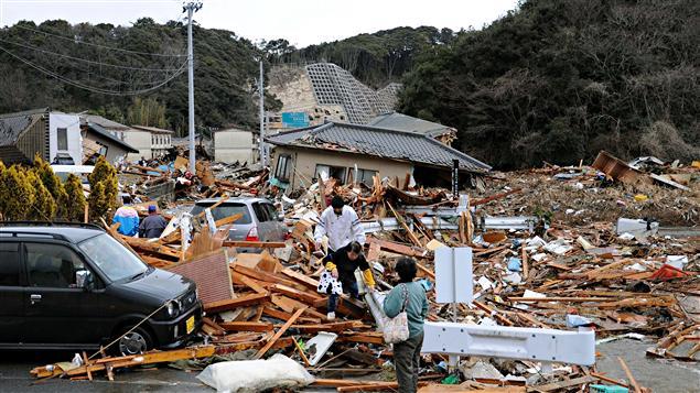 Des Japonais tentent de récupérer des affaires dans leur maison dévasté après le séisme dans la région de Fukushima au Japon.