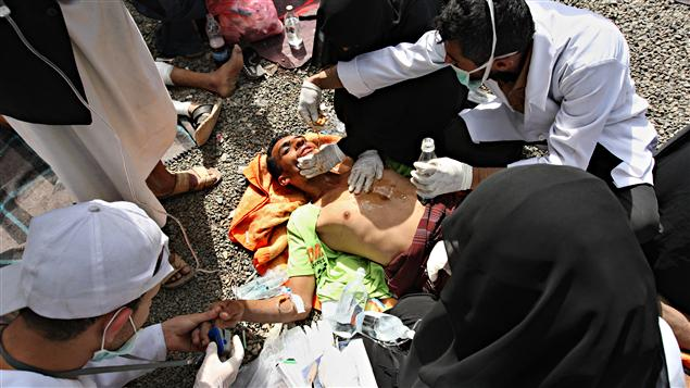 Un homme blessé se fait soigner sur le sol après l'assaut des autorités à Sanaa, au Yémen, le 12 mars 2011.