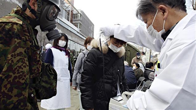Un médecin vérifie le taux de radiation d'une femme sous le regard d'un militaire, dans la préfecture de Fukushima.