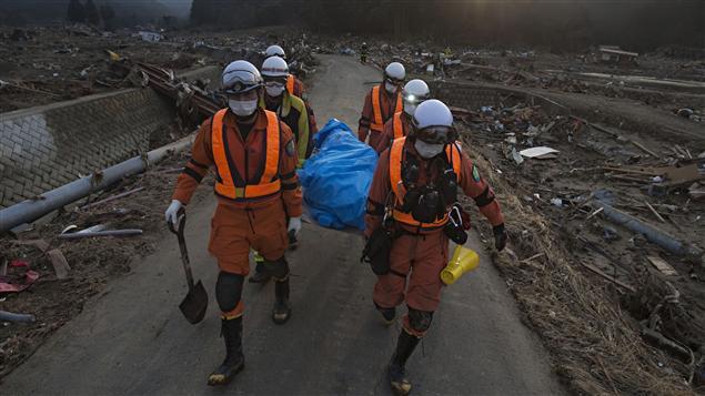 Des secouristes transportent le corp d'une victime dans le village de Saito.