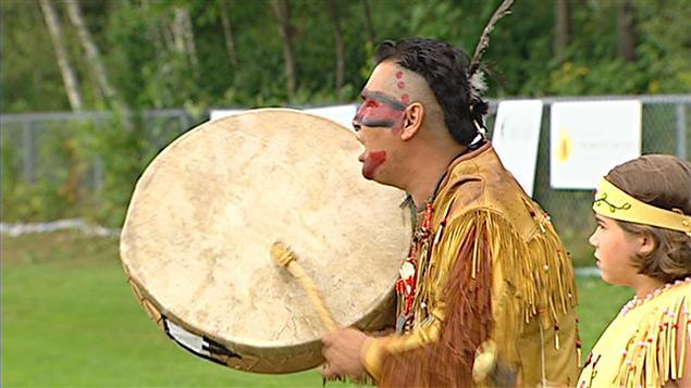 Un Amérindien chante et frappe sur un tambour