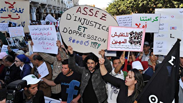 Des manifestants tiennent des pancartes en arabe et en français, réclamant plus de justice au Maroc