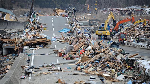 Des travailleurs étaient toujours en train d'enlever les débris des routes à Otsuchi jeudi.