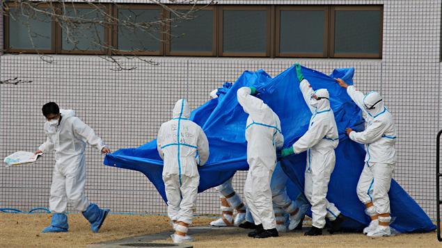 Des officiers des forces japonaises d'autodéfense escortent des travailleurs irradiés à la centrale de Fukushima, le 25 mars 2011, lors de leur transfert à l'hôpital universitaire de Fukushima.