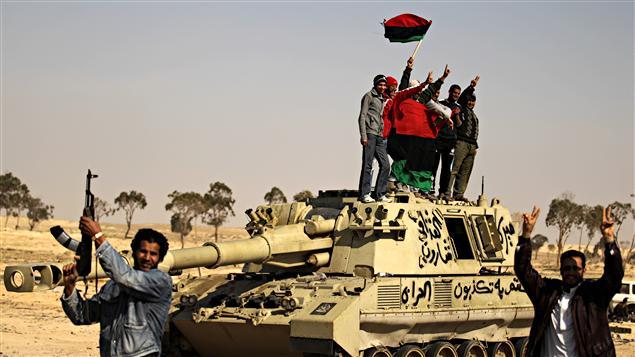 Des rebelles libyens célèbrent sur un tank détruit dans la ville d'Ajbadiya.