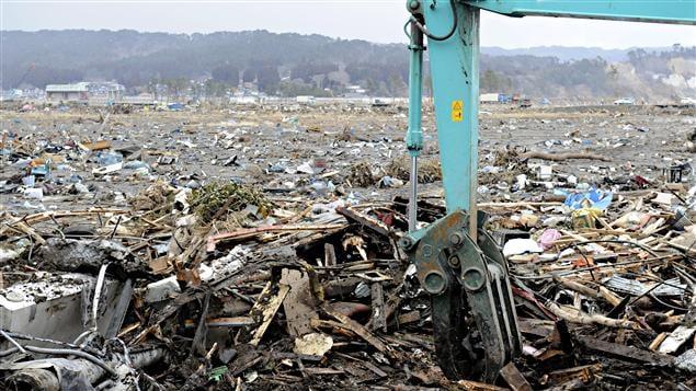 Une pelle mécanique ramasse les dégâts provoqués par le séisme et le tsunami dans le village de Noda.