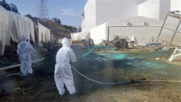 Des employés de Tepco pulvérisent de la résine sur le sol à proximité des bâtiments des réacteurs pour éviter la propagation de substances radioactives.