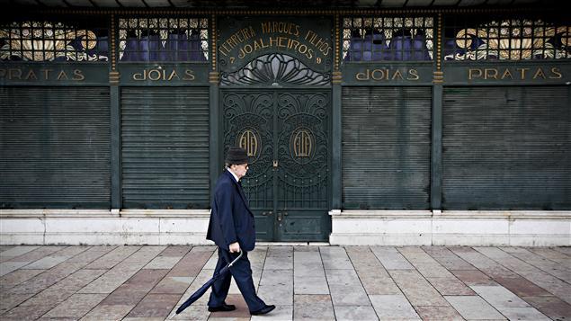 Un homme marche devant une bijouterie fermée de Lisbonne.