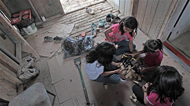 Des enfants autochtones jouent sur une véranda avec, au coin, un seau de toilette.
