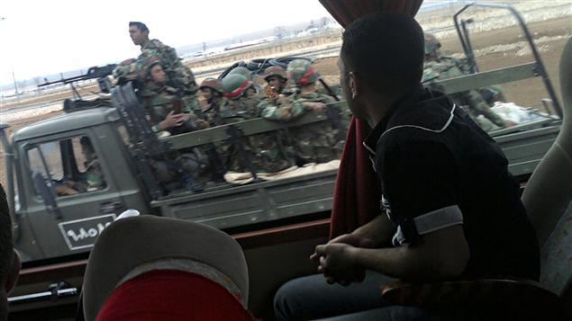 Sur cette photo prise avec un téléphone cellulaire, un Syrien assis dans un autobus observe un camion transportant des militaires près de Homs.