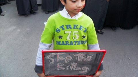 Un jeune garçon syrien porte une pancarte où il est écrit 'Arrêtez la tuerie' dans les rues de Daraya, près de Damas.