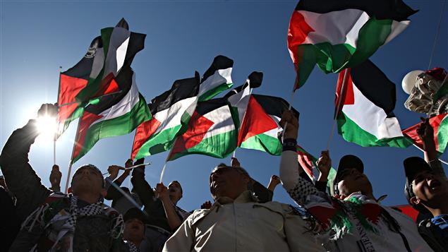 Des manifestants brandissent le drapeau palestinien lors d'une manifestation réclamant l'unité politique des Palestiniens le 15 mars dernier.