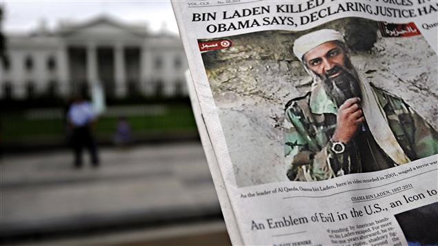 Près de la Maison-Blanche, un homme lisant un journal annonçant la mort de Ben Laden