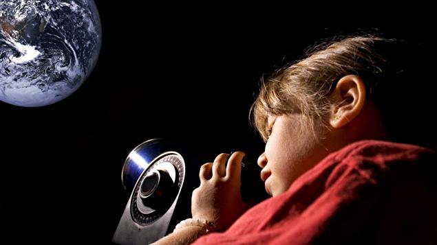 Une jeune fille observe la Lune à l'aide d'un télescope