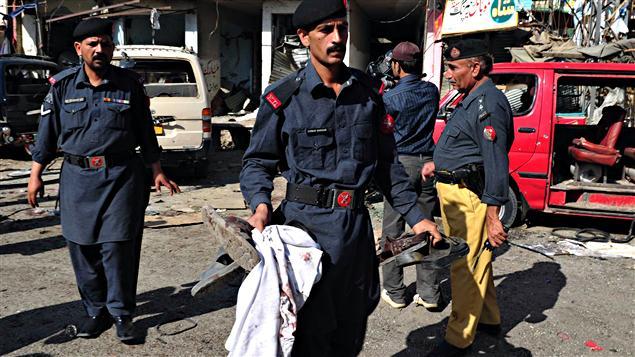 Des agents de sécurité pakistanais collectent les effets personnels des victimes de l'attaque de vendredi commis devant un centre d'entraînement de la police des frontières à Shaqbadar, dans le nord-ouest du Pakistan.